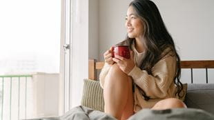 Girl sitting in bed drinking and smiling