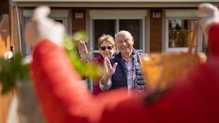 elderly couple waving from their home