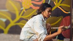 Woman painting a mural on a wall