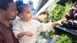 Girl reaching for healthy vegetables in supermarket