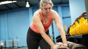 Woman reaching for dumbbell in gym