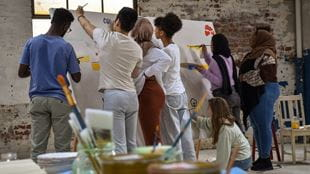 Group of young people painting a mural