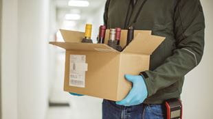Man wearing gloves delivering box of alcohol