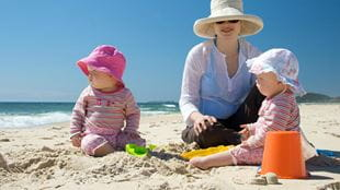 Mother and two children in hats on the beach
