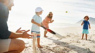 Family playing a game of beach cricket