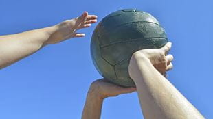 Hands holding up a netball