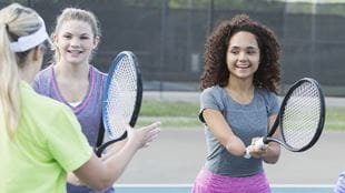 Two girls playing tennis